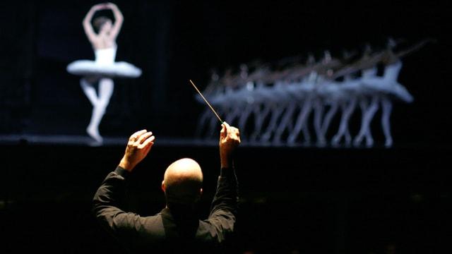 Ein Dirigent von hinten fotografiert, auf der Bühen Belletttänzerinnen.