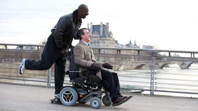 EIn junger, schwarzer Mann steht lachend hinten auf den fahrenden Rollstuhl eines älteren, weissen MAnnes, der ebenfalls lacht.