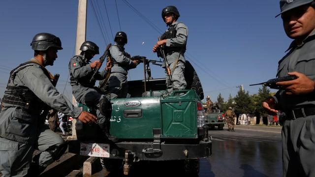Polizisten steigen von einem Jeep