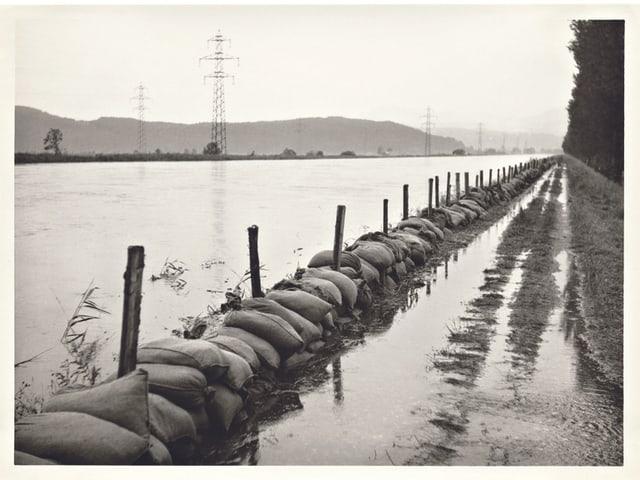 Schwarz-Weiss-Bild, Sandsäcke in einem Fluss.