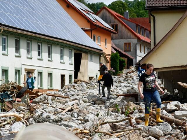 Dorfbewohner gehen über Geröll, wo einst eine Strasse war.