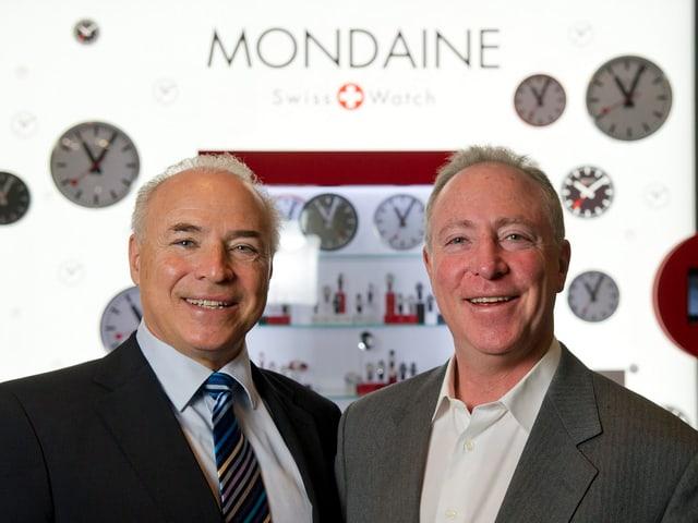 Ronnie und André Bernheim stehen nebeneinander, hinter ihnen sieht man die Wanduhren von Mondaine.