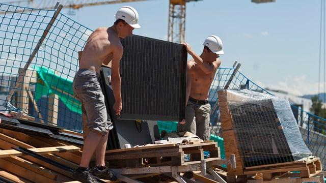 Zwei junge Männer heben auf einem Dach ein Solarpanel vom Palett