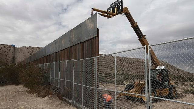 Arbeiter bauen an einem Zaun.