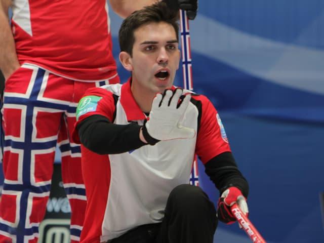 Peter De Cruz kniet auf dem Eis und macht Handzeichen.