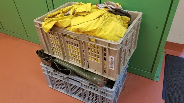Kiste mit Gummistiefel und Regenmänteln
