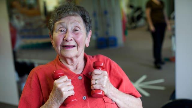 Nahaufnahme einer älteren Frau, die freudestrahlend zwei kleine Hanteln in den Händen hält.