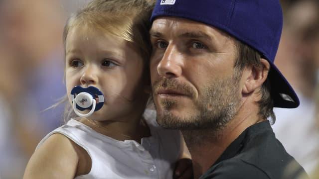 David Beckham trägt seine Tochter Harper auf dem Arm