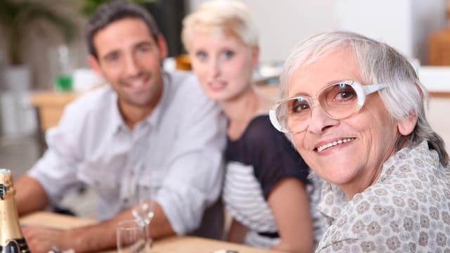 Grossmutter im Vordergrund, Paar unscharf im Hintergrund