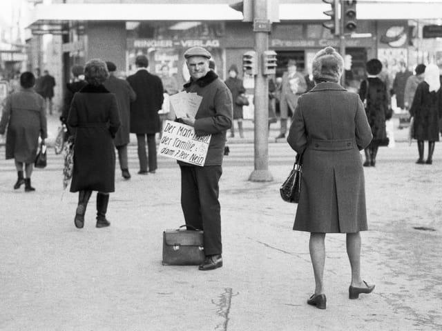 Ein Mann mit Schild und Flugblättern in einer belebten Fussgängerzone.