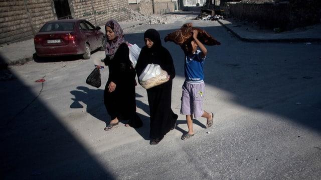 Zwei Frauen und ein Knabe auf einer staubigen Strasse.