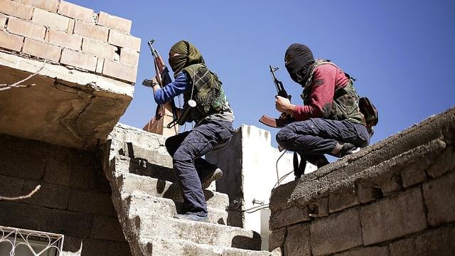 Zwei maskierte Kämpfer der verbotenen türkischen Arbeiterpartei PKK mit Gewehren auf der Terrasse eines Hauses in Nusaybin im Bezirk Diyarbakir.