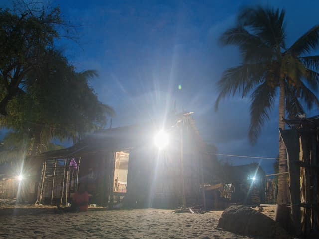 Lichtquellen an Häusern, die von Palmen umgeben sind.