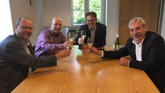 Vier Männer trinken Weisswein an einem Tisch