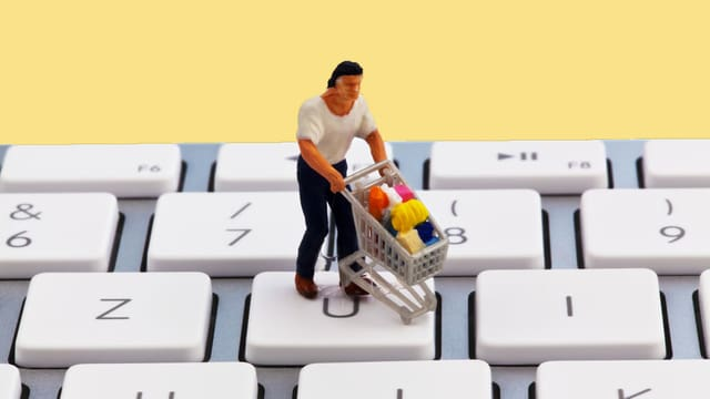 Eine Spielzeugfigur mit Einkaufswagen auf einer Computertastatur