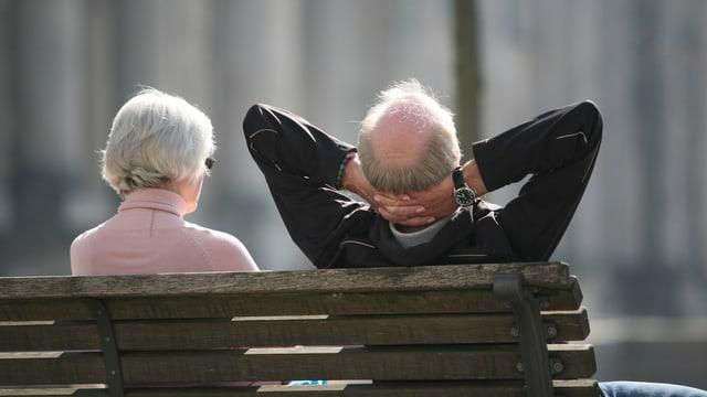 Älterer Mann und ältere Frau sitzen auf einer Bank, fotografiert von hinten.