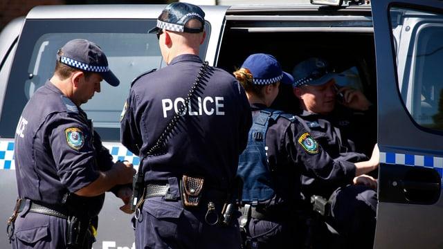 Polizisten besprechen einen Einsatz bei einem Polizeifahrzeug