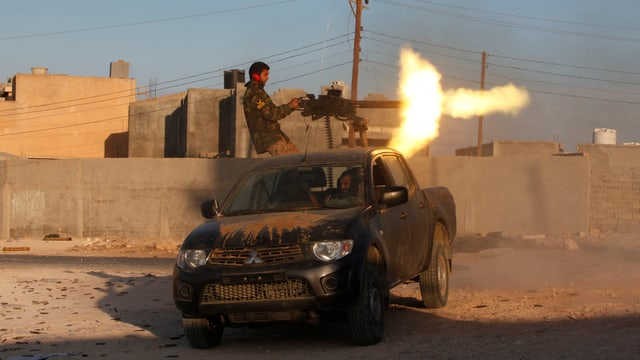 Ein Kämpfer feuert ein Geschütz auf einem Fahrzeug ab.