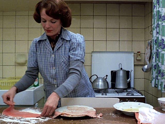 Eine Hausfrau paniert Fleisch.