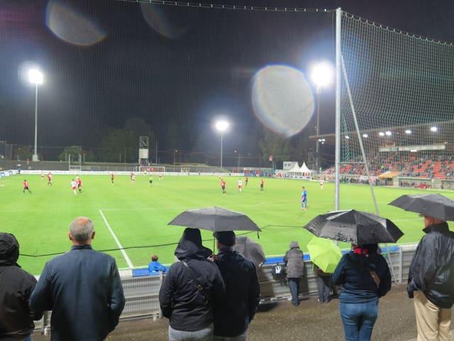 Ein paar Fans stehen im Regen.