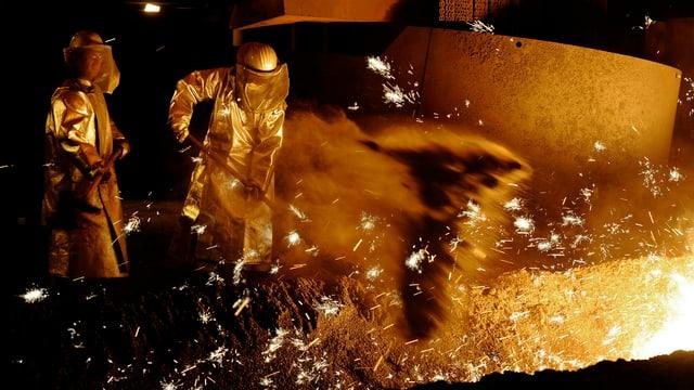 Stahlarbeiter arbeiten an einem Hochofen.