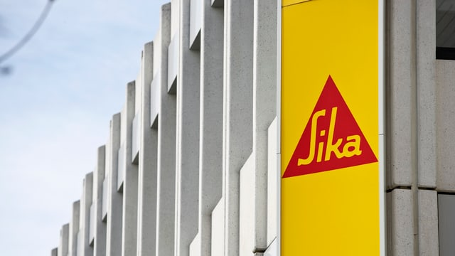 bajetg da beton ed il logo da Sika, triangul cotschen cun scrit Sika sin fund mellen
