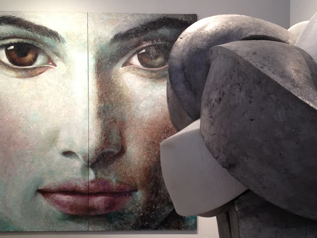 Eine Skulptur vor einem grossen Gemälde.