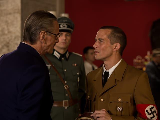 Filmstill: Ein Mann im dunklen Anzug unterhält sich mit einem Mann in Nazi-Uniform.