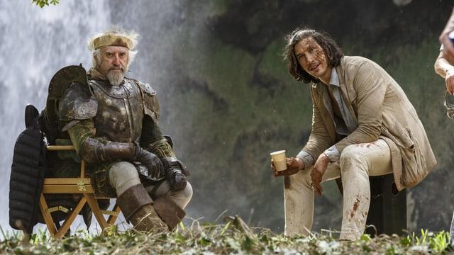 Zwei Männer sitzen lachend draussen vor einem Wasserfall auf zwei Stühlen.