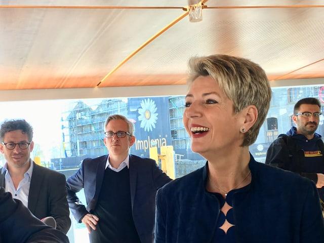 Frau im Vordergrund, drei Männer im Hintergrund