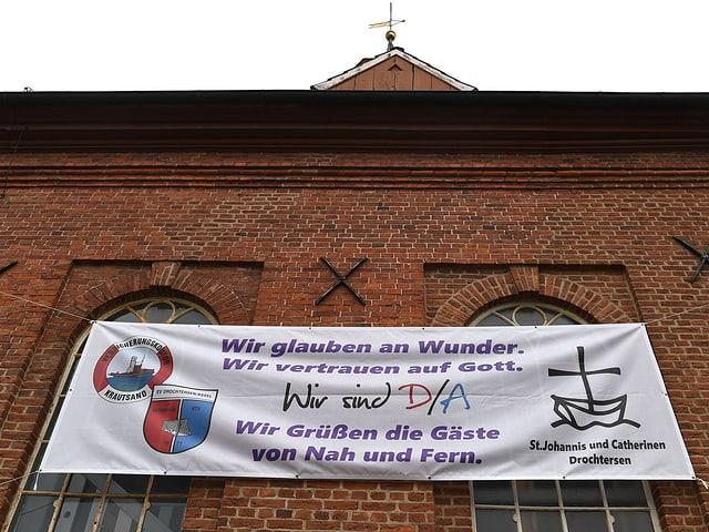 Auf einem Banner an der örtliche Kirche in Drochtersen steht: «Wir glauben an Wunder».