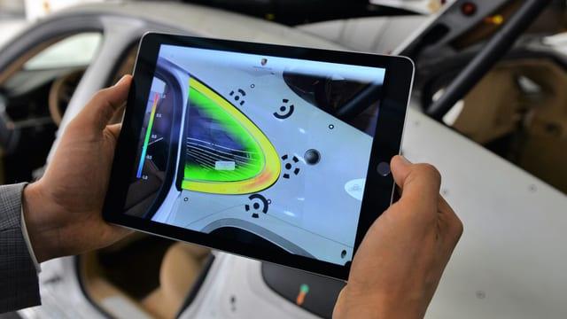 Ein Tablet scant die Oberfläche eines Autos und färbt Bereiche grün ein.
