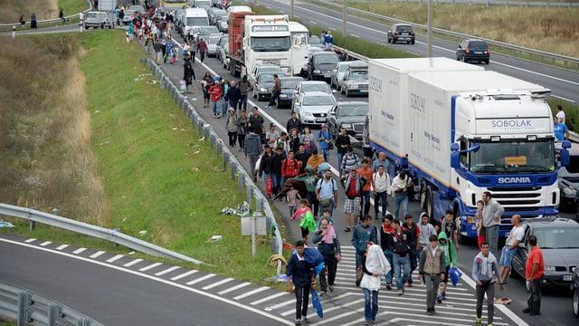 Fugitivs van a pe sin l'autostrada per vegnir da l'Ungaria en l'Austria.