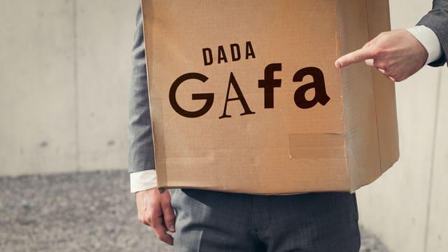 Ein Pappkarton aus dem Hände und Arme herausschauen. Darauf ein Schriftzug: «Dada-Gafa».