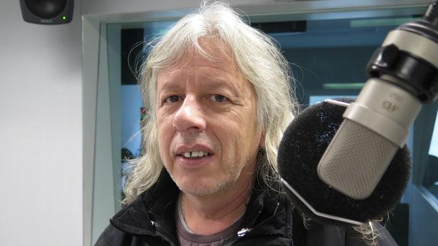 Mann im Radiostudio neben Mikrofon.