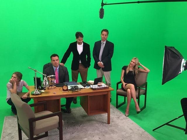 Schauspieler stehen um einen Schreibtisch rum, der Hintergrund ist grün.