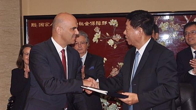 Cusseglier federal Alain Berset ed il minister dal socialesser Yin Weimin suenter avair suttascrit la cunvegna.