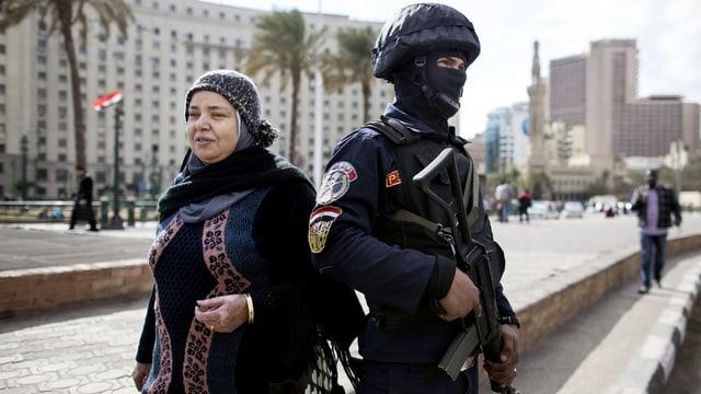 Eine ägyptische Frau läuft neben einem schwer bewaffneten Sicherheitsbeamten vorbei.