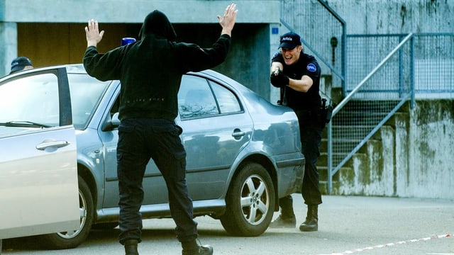 In policist che drizza la pistola sin in um tut en nair cun capuza.