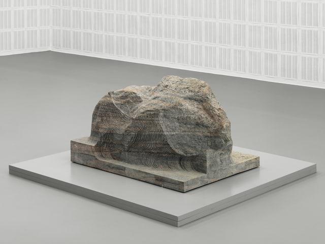 Ein schroff geschliffener Stein in einem Ausstellungsraum.