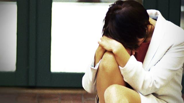 Eine erschöpfte Frau lehnt ihren Kopf auf ihr Knie.