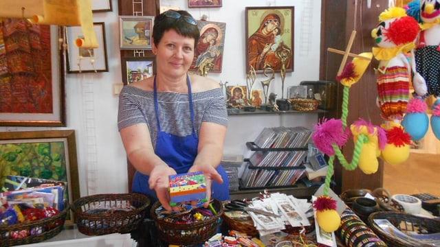 Eine Frau mit blauer Schürze steht in ihrem Laden und hält ein bemaltes Kästchen in der Hand.