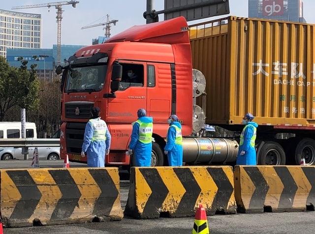 Personen in Schutzanzügen neben Lastwagen