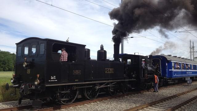 Zwei Dampflokomotiven ziehen einen blauen Wagen