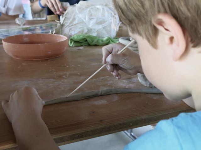 Ein Junge bearbeitet eine Wurst aus Ton