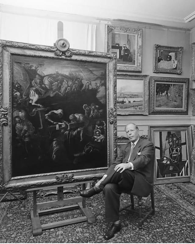 Mann sitzt inmitten von Kunstwerken