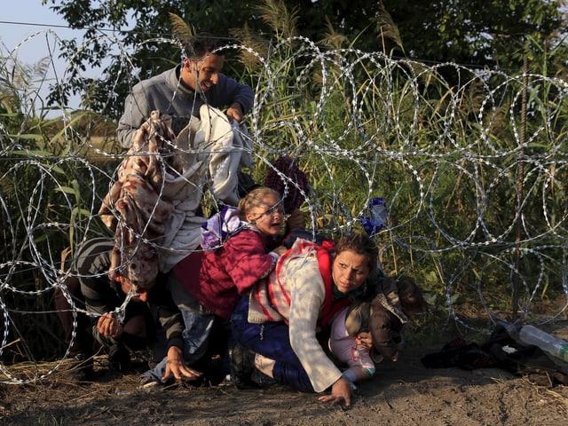 Syrische Flüchtlinge im Sommer 2015 bei einem Zaun an der serbisch-ungarischen Grenze.