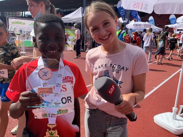 Kinderreporterin und Junge grinsen mit Mikrofon und Medaille in die Kamera