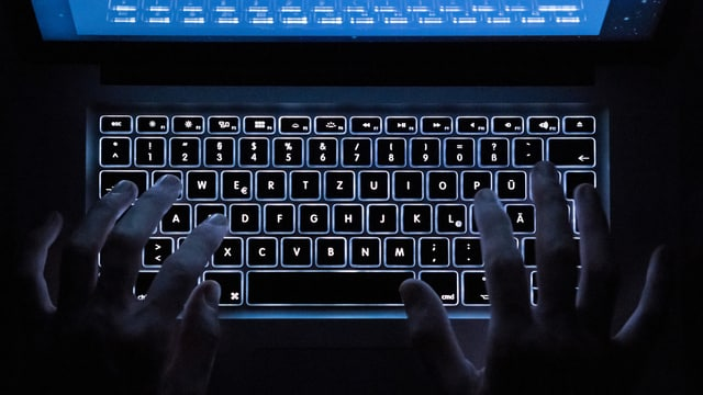 mauns sin ina tastatura illuminada d'in laptop