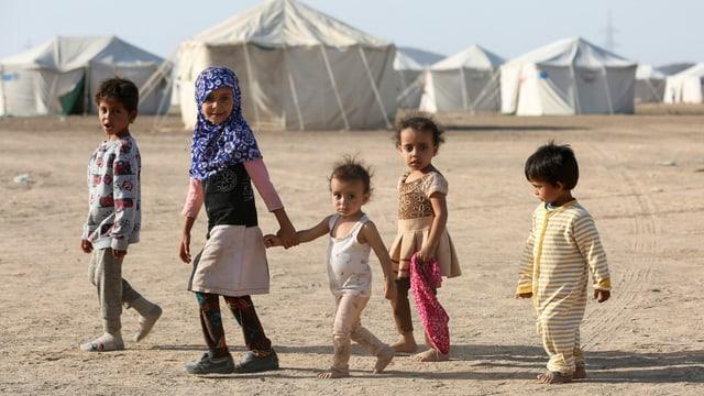 Eine Gruppe von 5 Kindern vor Zelten.